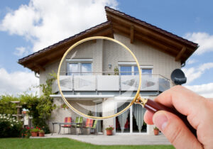 Hand With Magnifying Glass Over House